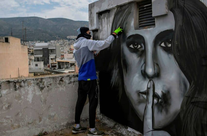 A man graffitis 'violence' depiction on a wall in Athens (REUTERS)